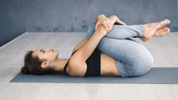 Woman practicing yoga, lying in knees to chest pose Apanasana exercise. Woman practicing yoga, lying in knees to chest pose in yoga studio apanasana stock pictures, royalty-free photos & images