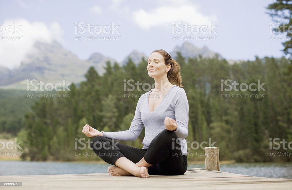 Woman practicing yoga on pier by lake royalty-free stock photo