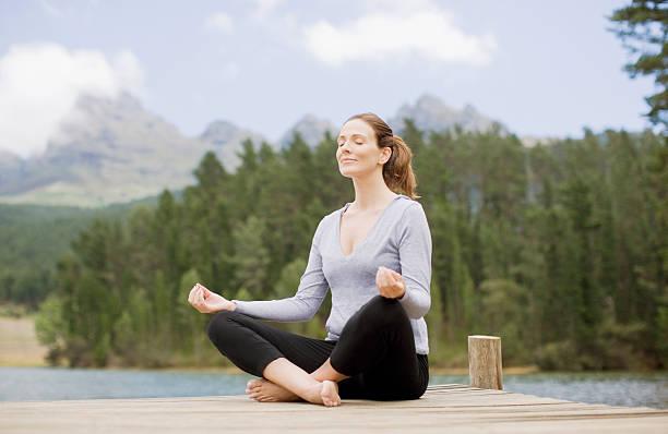 woman practicing yoga on pier by lake - mid volwassen vrouw stockfoto's en -beelden