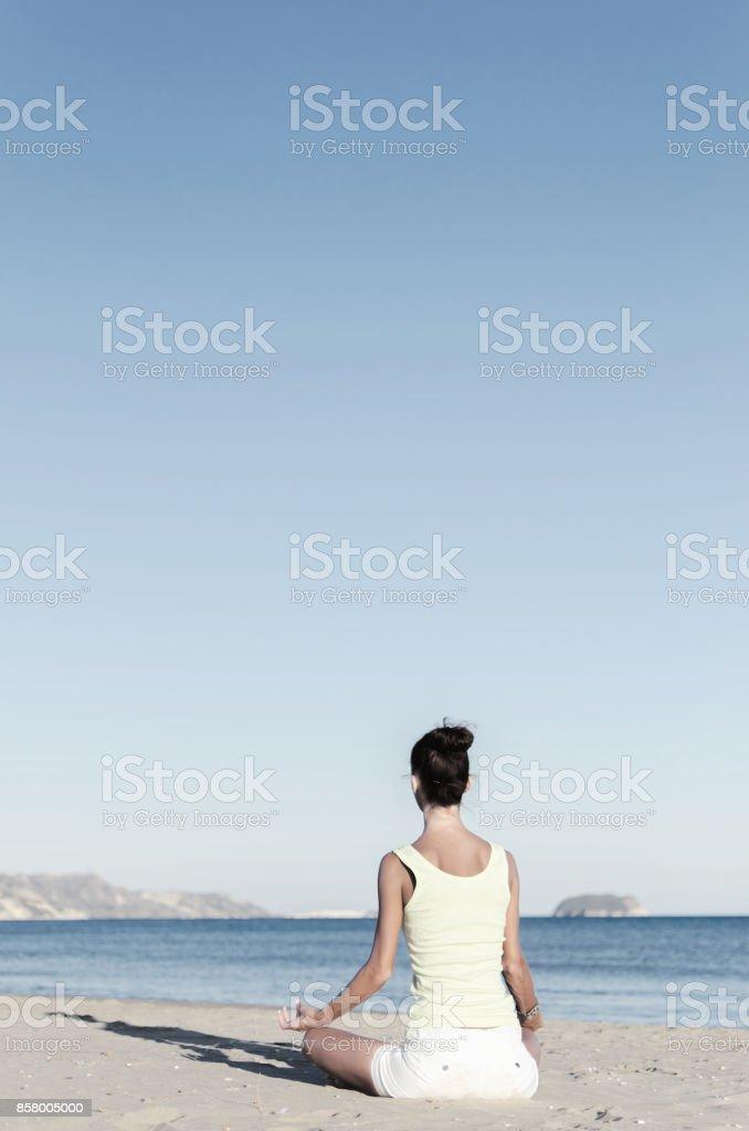 Mulher praticando ioga na praia de areia - foto de acervo