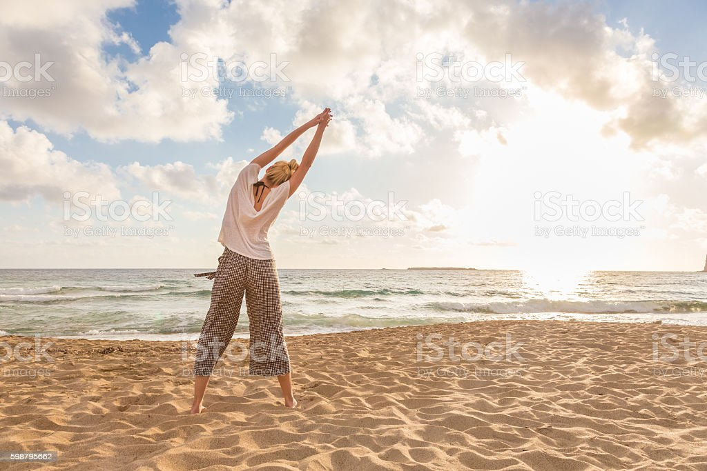 Woman practicing yoga on sea beach at sunset. stock photo