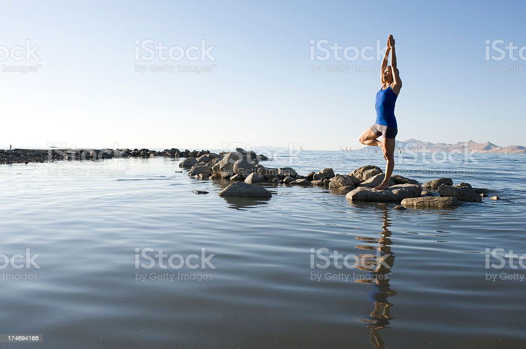 Woman practicing yoga on stones in a river royalty-free stock photo