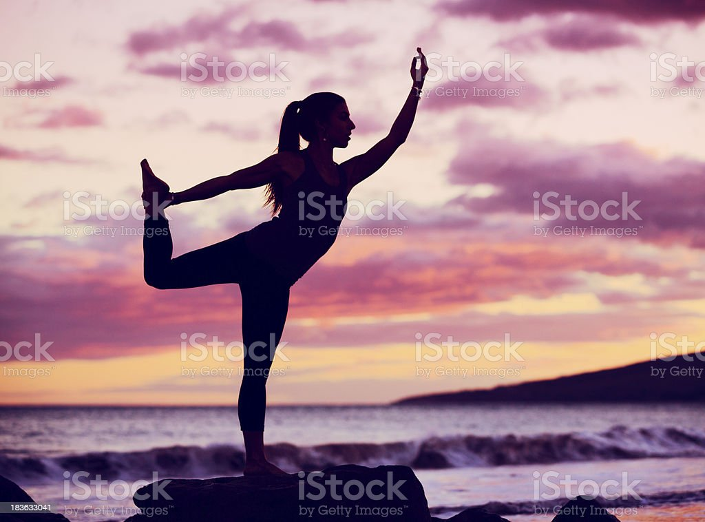 Woman practicing yoga on the beach at sunset royalty-free stock photo