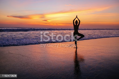 istock woman practicing yoga on the beach in Bali, Indonesia 1152472628