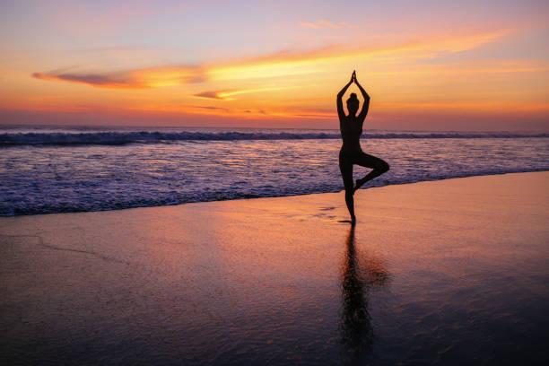 woman practicing yoga on the beach in Bali, Indonesia stock photo