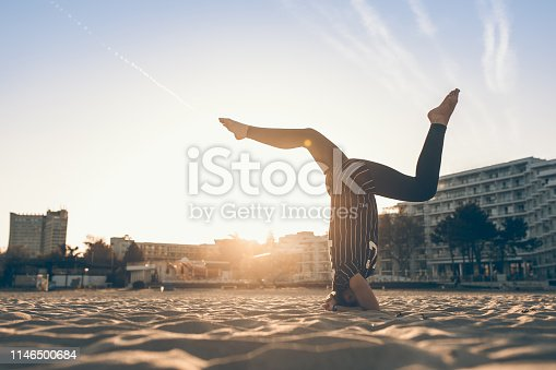 Young woman practicing yoga on the beach, Albena, Bulgaria.