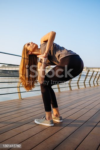 Woman Performing Outdoor Yoga, Parivrtta Anjaneyasana (Revolved Crescent Lunge)