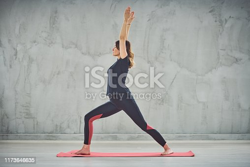 Side view of Caucasain brunnette standing on the mat in Crescent Lunge yoga posture.