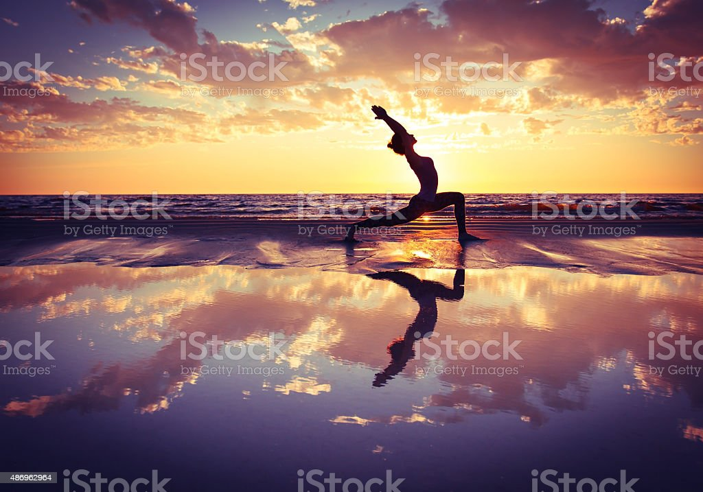 woman practicing yoga silhouette of woman practicing yoga on the beach at sunset 2015 Stock Photo