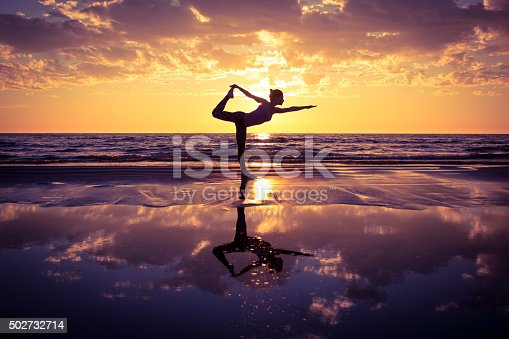 istock woman practicing yoga 502732714