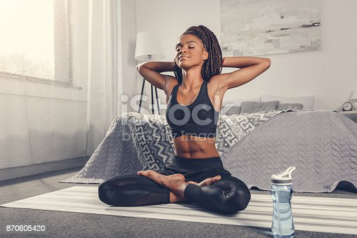 istock woman practicing yoga 870605420
