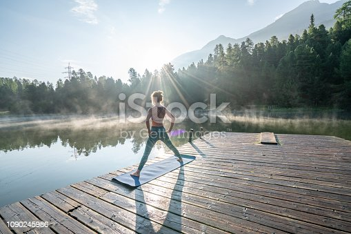 One young woman exercising yoga on a lake pier in the morning, fog on water surface. People wellbeing relaxation healthy lifestyle concept. Shot in Graubunden Canton, Switzerland.