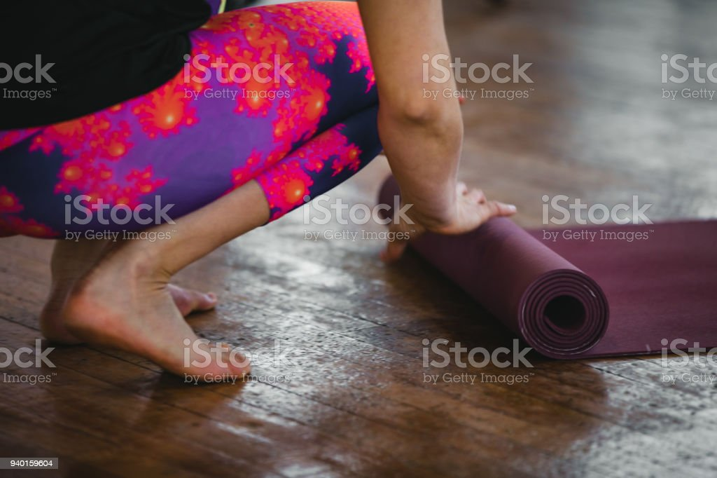 Woman practicing yoga. Preparation. Rolling and unrolling of the yoga mat stock photo