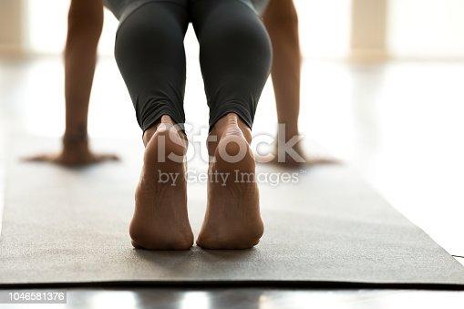 675173150istockphoto Woman practicing yoga, Push ups or press ups, close up 1046581376