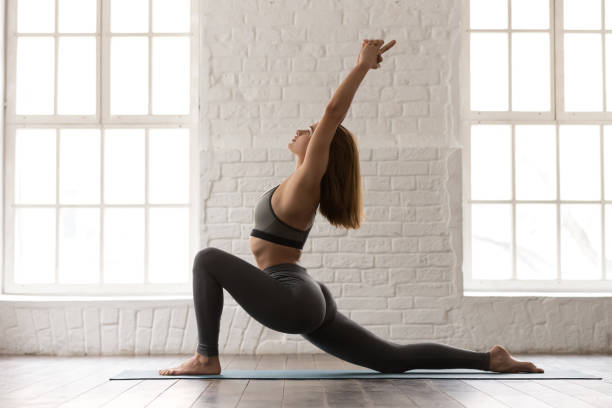 Woman practicing yoga, standing in anjaneyasana pose, Horse rider exercise Woman in grey sportswear, bra and leggings practicing yoga, standing in anjaneyasana pose, girl doing Horse rider exercise on mat, working out at home or in yoga studio with white walls sun salutation stock pictures, royalty-free photos & images
