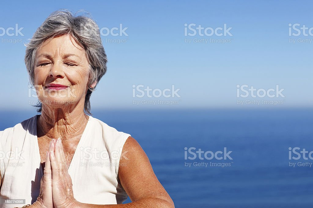 Woman practicing yoga with ocean in background royalty-free stock photo