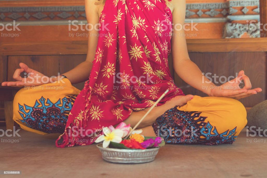 Woman practicing yoga with with canang sari - offering for Gods. Balinese tradition. stock photo