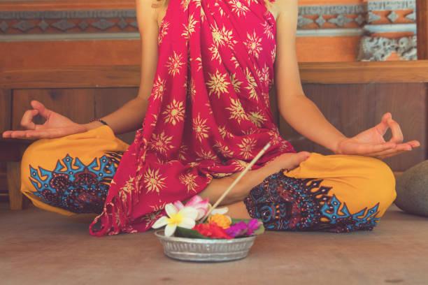 woman practicing yoga with with canang sari - offering for gods. balinese tradition. - традиционная церемония стоковые фото и изображения