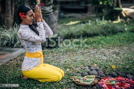 Woman practicing yoga with with canang sari - offering for Gods. Balinese tradition.