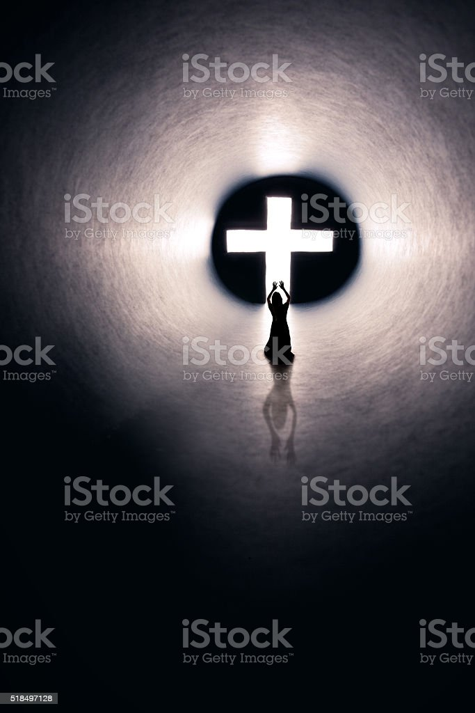Woman Praising Christian Cross In Lighted Tunnel stock photo