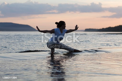 Woman praticing tai chi chuan at sunset on the beach. Chinese management skill Qi's energy. solo outdoor activities. Social Distancing