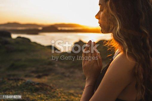 Woman praying alone at sunrise. Nature background. Spiritual and emotional concept. Sensitivity to nature