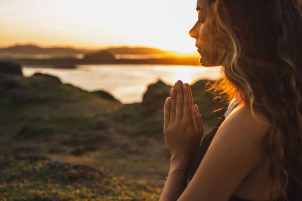 vrouw die alleen bij zonsopgang bidt. natuur achtergrond. spiritueel en emotioneel concept. gevoeligheid voor de natuur - heilige stockfoto's en -beelden