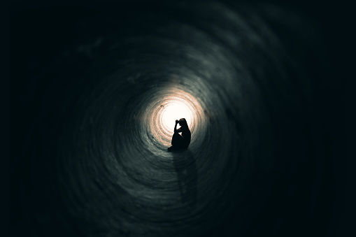 The silhouette of a praying woman sitting in a dark tunnel with a light at the end.