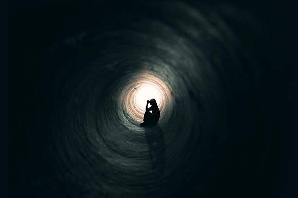 frau beten im einer dunklen ort - depression stock-fotos und bilder
