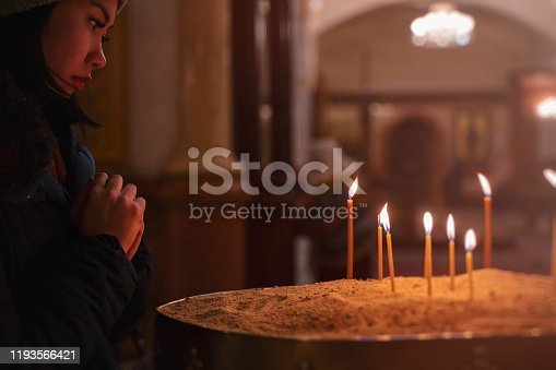 Woman praying in Church, candles in Cathedral, hope concept