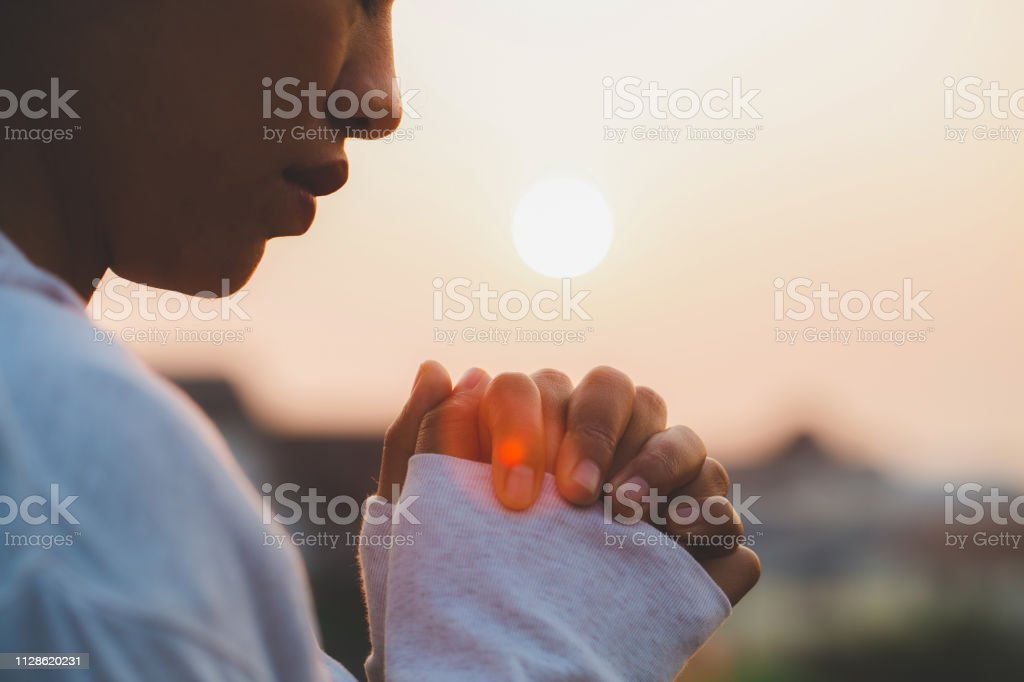 Woman praying in the morning on the sunrise background. Christianity concept. Pray background. Faith hope love concept. Woman praying in the morning on the sunrise background. Christianity concept. Pray background. Faith hope love concept. Adult Stock Photo