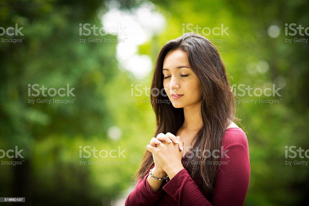 Woman praying outdoors stock photo