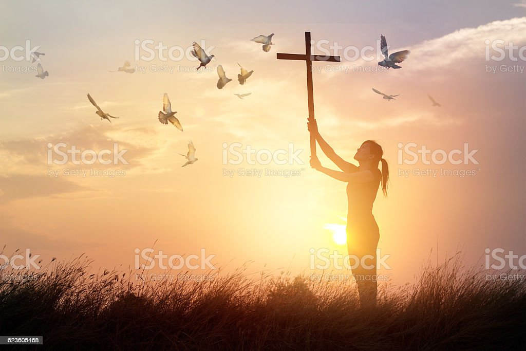 Woman praying with cross and flying bird in sunset background stock photo