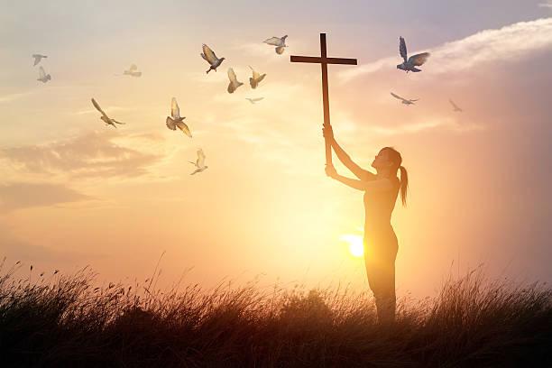 woman praying with cross and flying bird in sunset background - religionsfreiheit stock-fotos und bilder