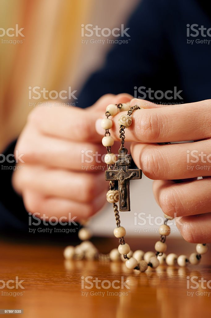 Woman praying with rosary to God royalty-free stock photo