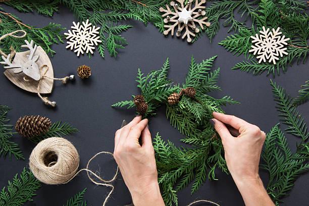 woman prepare a christmas wreath from cone and snowflakes. overhead. - winterdeko basteln stock-fotos und bilder