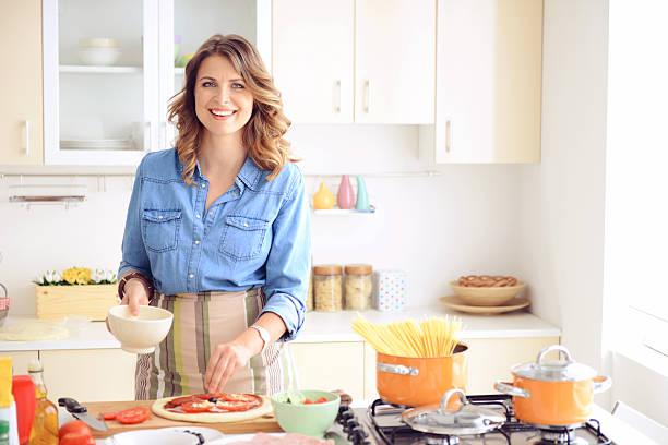 mulher prepara a comida na cozinha - dona de casa - fotografias e filmes do acervo