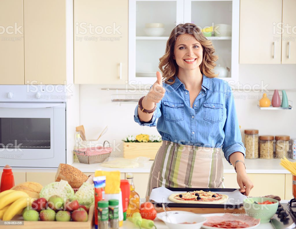 woman prepares food in the kitchen stock photo