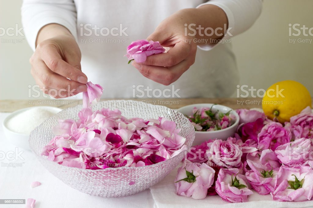 A woman prepares jam from roses, ingredients for jam from roses. Rustic style. - Foto stock royalty-free di Adulto