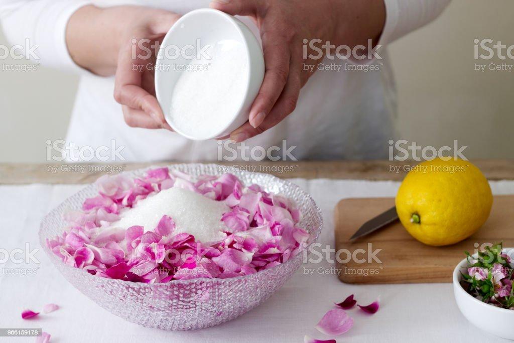 En kvinna förbereder sylt från rosor, ingredienser för sylt från rosor. Rustik stil. - Royaltyfri Aromaterapi Bildbanksbilder