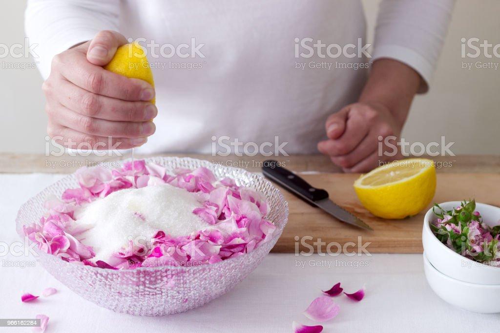 Een vrouw bereidt jam van roses, ingrediënten voor jam van rozen. Rustieke stijl. - Royalty-free Achtergrond - Thema Stockfoto