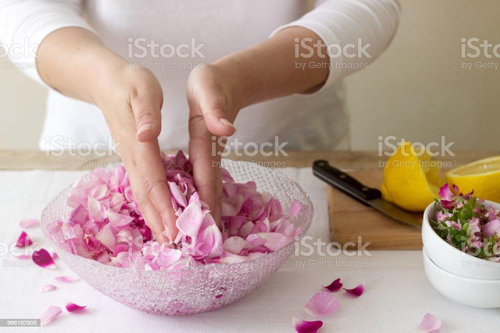 Una mujer prepara mermelada de rosas, ingredientes para la mermelada de rosas. Estilo rústico. - Foto de stock de Adulto libre de derechos