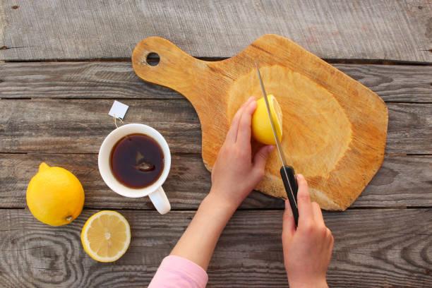 Woman prepares tea with lemon. Top view. stock photo
