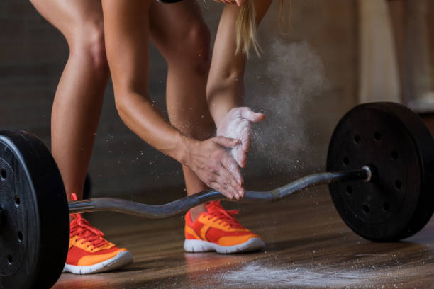 Woman prepares to deadlift  with barbell stock photo