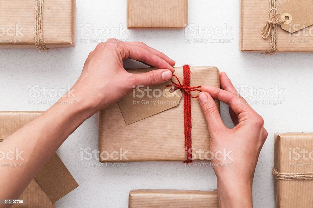 Woman preparing a gift and tying a bow. Wrapping ideas. stock photo