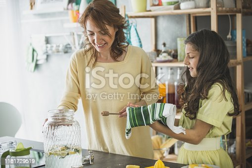 Mid adult woman and her teenage daughter having bonding moments while preparing lemonade. They are adding honey to sweeten everything up.
