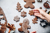 Woman preparing Christmas gingerbread cookies in kitchen. Female hand placing freshly made cookies with spices on table.