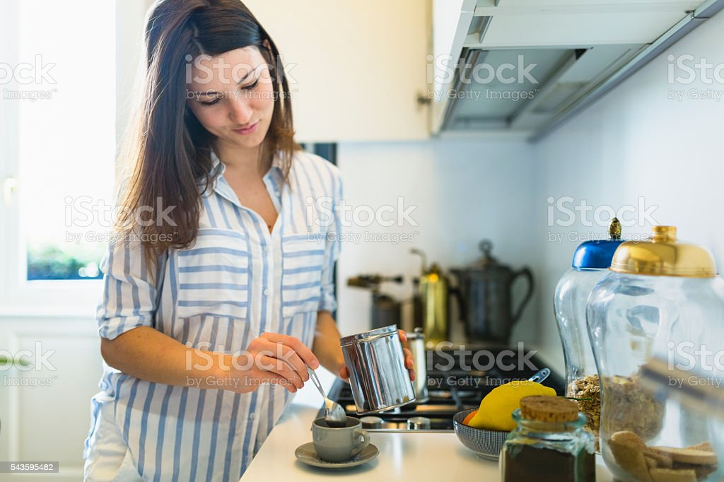 Woman preparing coffee at home in the kitchen stock photo