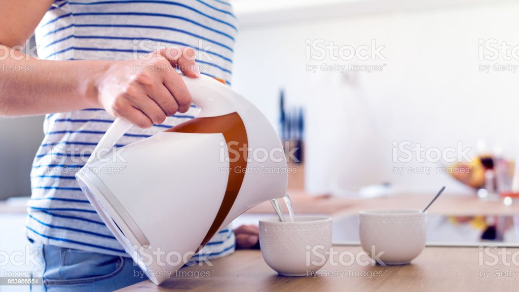 Woman preparing coffee or tea. Pouring water into a cup. stock photo