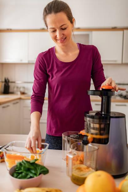 femme préparant le jus pressé froid - cold pressed photos et images de collection